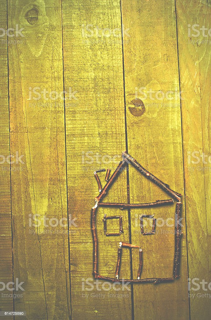 House arranged from twigs on green wooden backdrop. stock photo