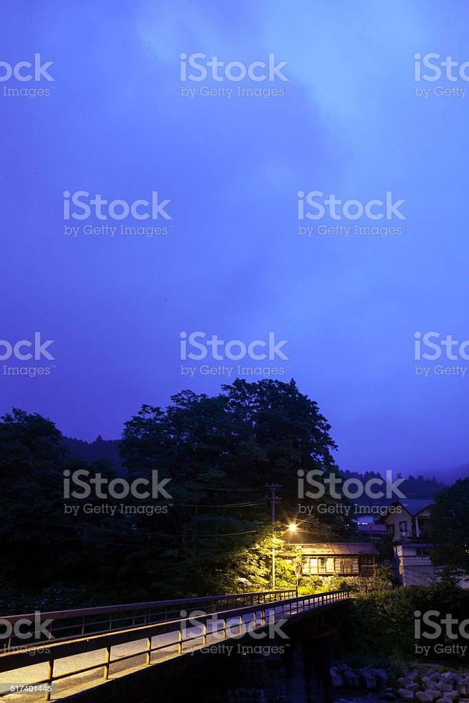 House at the end of a bridge at dusk stock photo