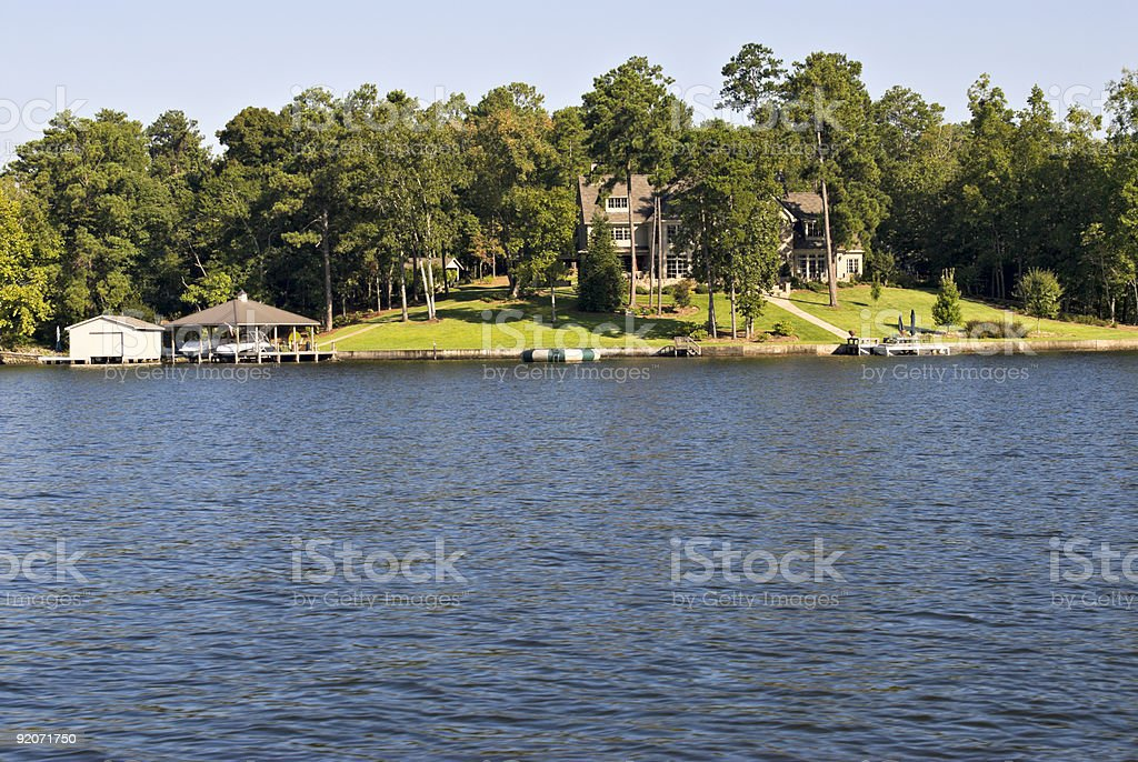 house behind trees along a river with a boat dock stock photo