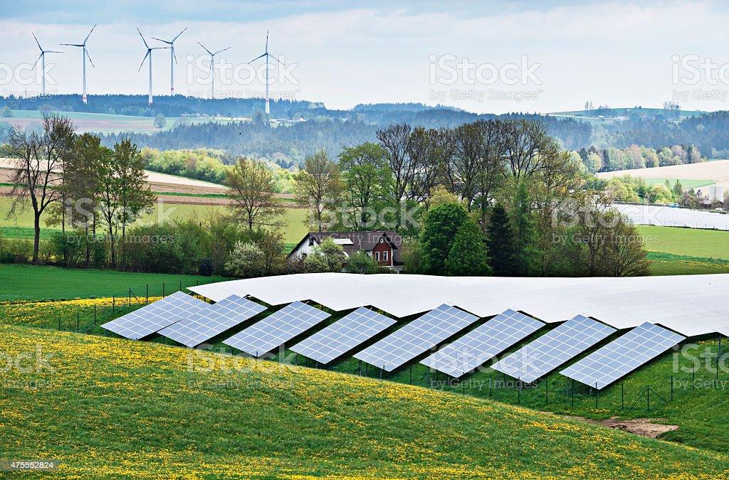 House between solar panels and wind turbine stock photo