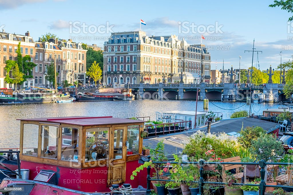 House boat at the river Amstel with the Amstel Hotel stock photo
