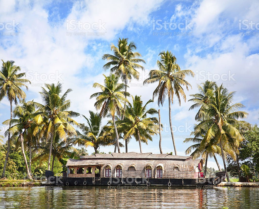 House boat on river in tropics with palm trees royalty-free stock photo