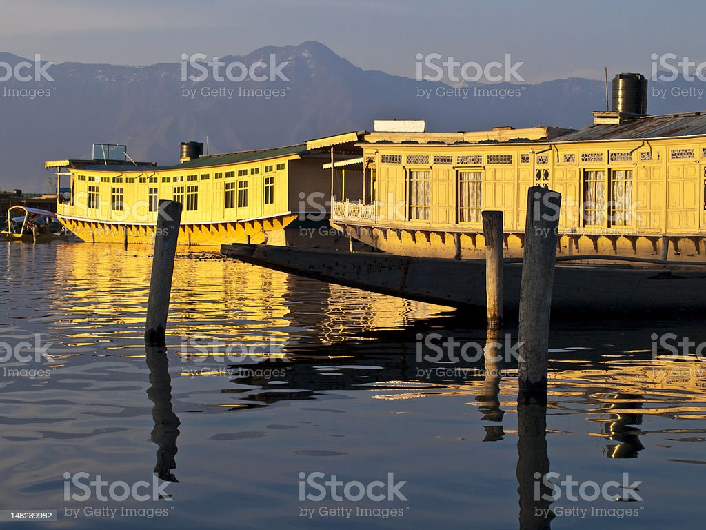 House boat on water with mountain views in distance stock photo