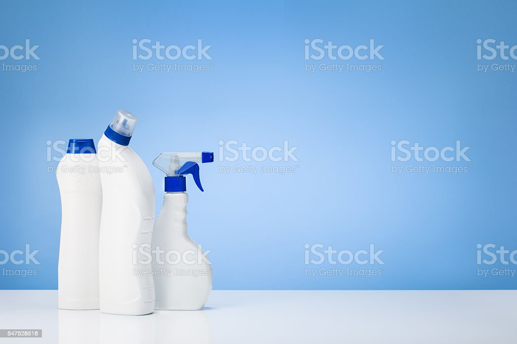 House cleaning products on white table with blue gradient backdrop stock photo