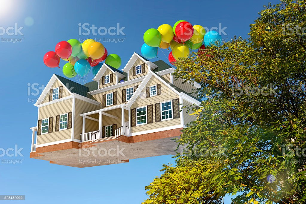 House flying in the sky with balloons, behind trees stock photo