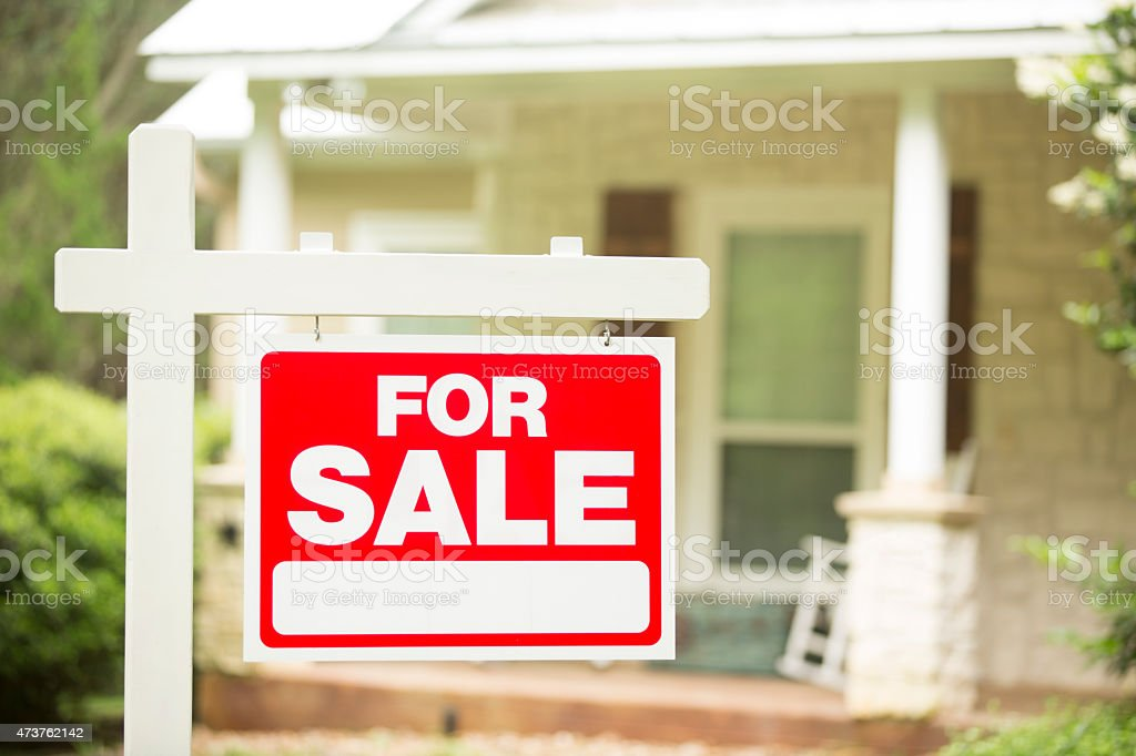 House for sale. Real estate sign. Front yard. No people. stock photo