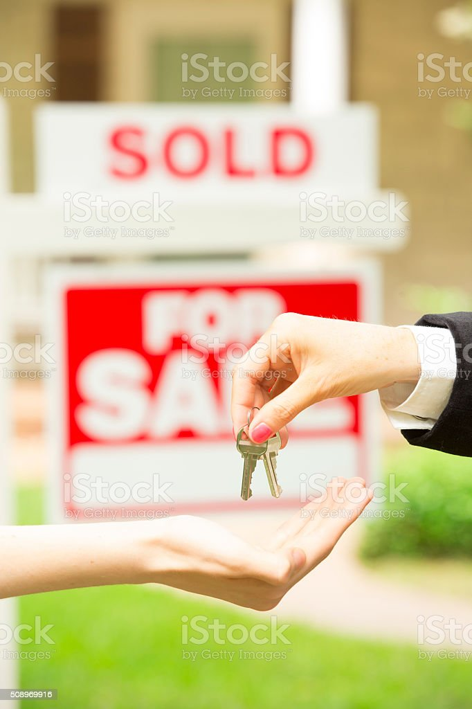 House for sale sign. Realtor gives buyer keys. Home.  Sold. stock photo