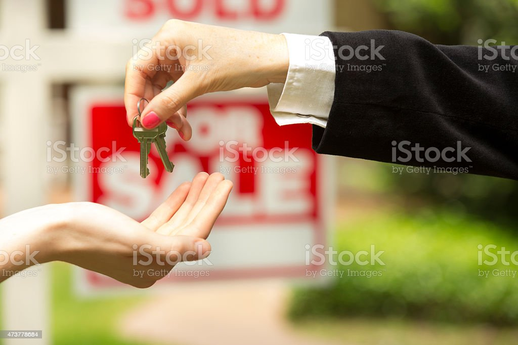 House for sale, sold sign. Realtor gives buyer keys. Home. stock photo