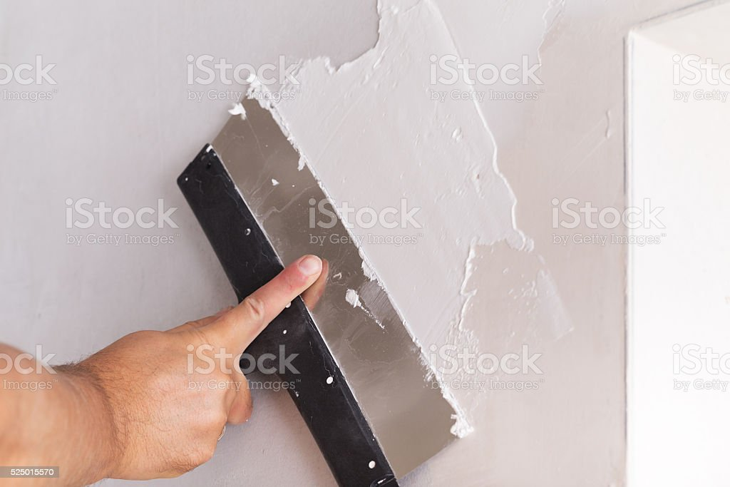 house improvement worker puts finishing layer of stucco on wall stock photo