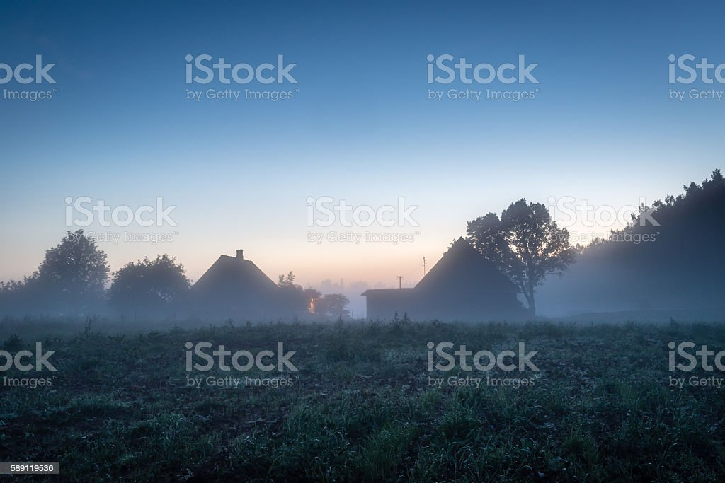 House in Latvian countryside at foggy evening stock photo