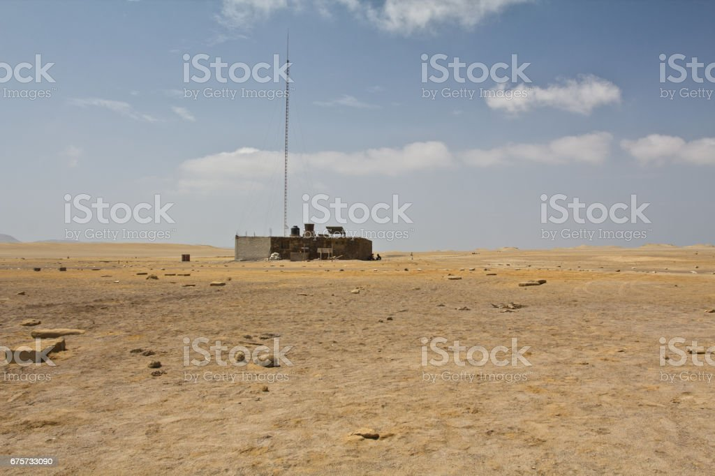 House in sandy desert close to the cliffs. Perfect place to see tropical desert, wide cliffs and coloful beaches on the rocky islands and national reserve. Small islands near the town of Paracas. stock photo
