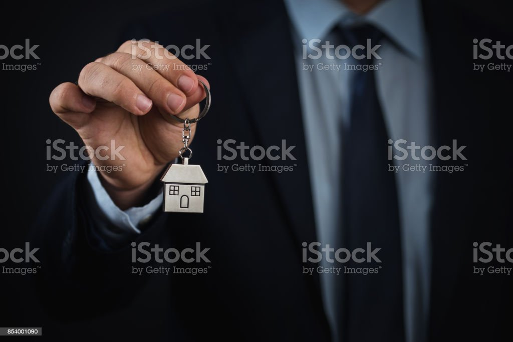 House key in businessman hand with clipping path stock photo