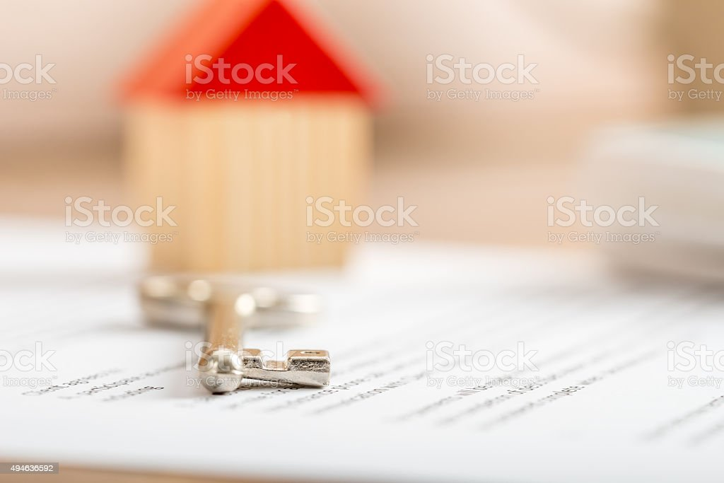House key lying on a contract stock photo
