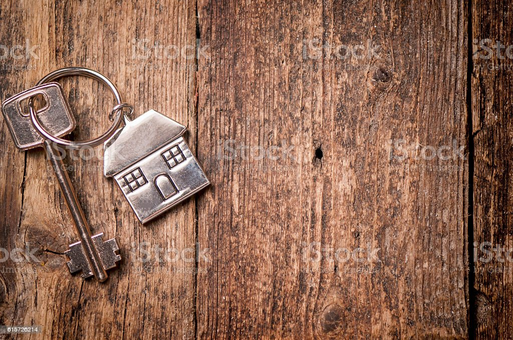 House key on a house shaped keychain on wooden table stock photo