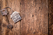 House key on a house shaped keychain on wooden table