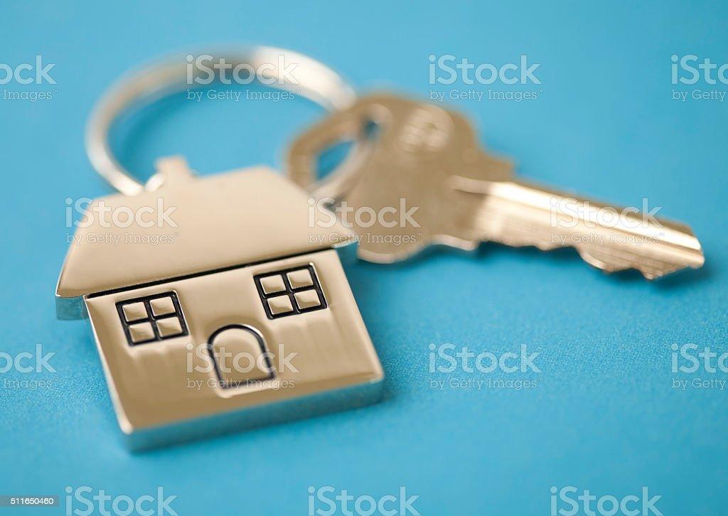 House keys with house shaped key chain on blue stock photo