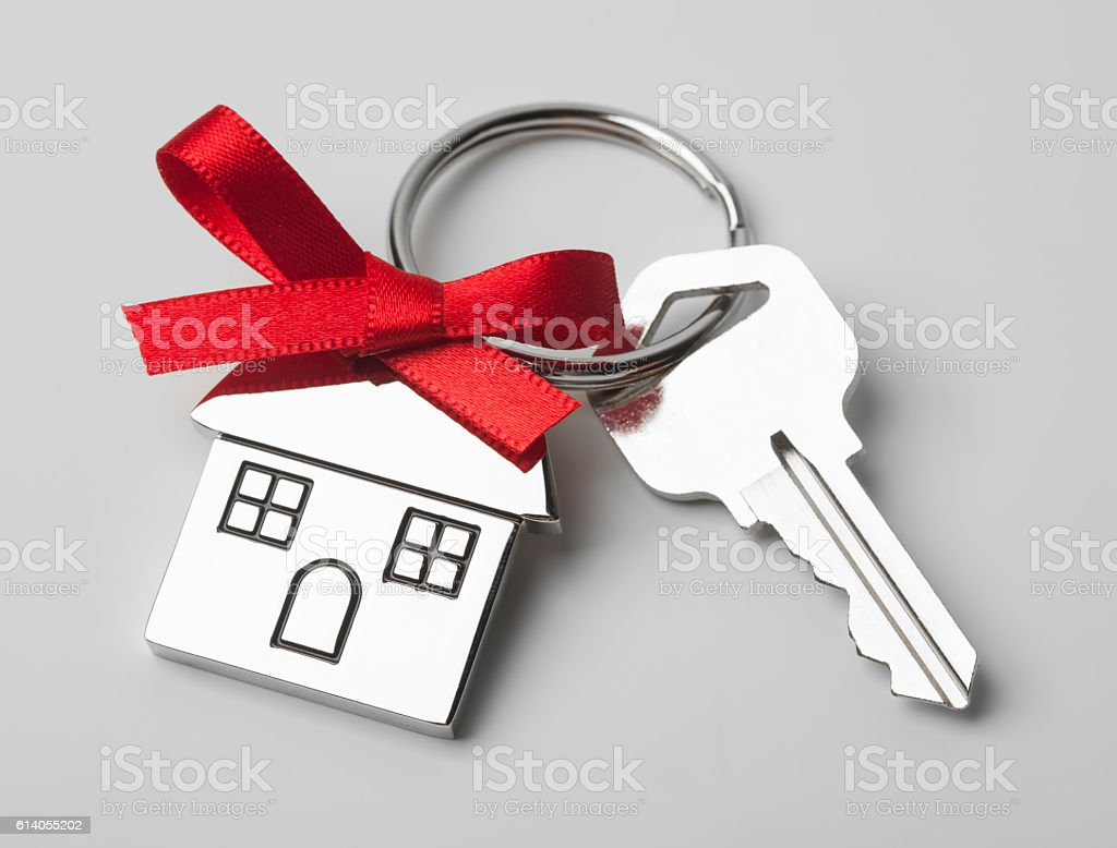 House keys with red ribbon on light background stock photo