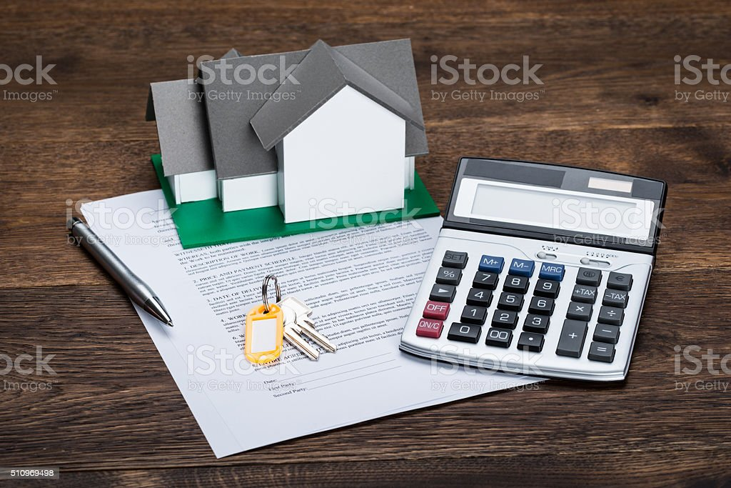 House Model On Contract Paper With Keys And Calculator stock photo