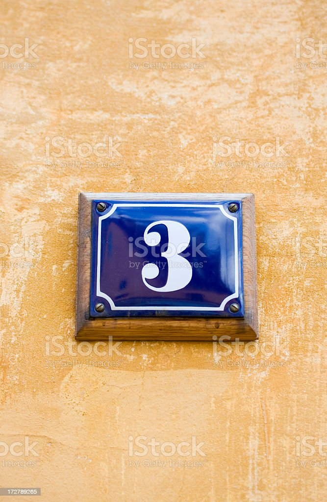 House number 3. Blue enamel sign on yellow wall. royalty-free stock photo