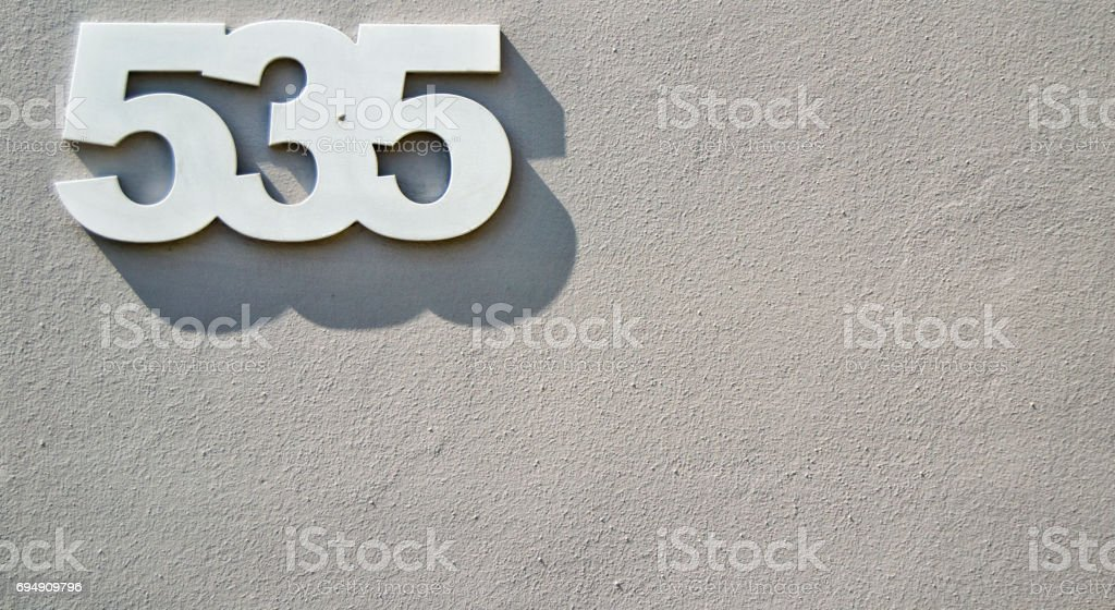 House numbers five hundreds and thirty five (535 five three five) on a gray background stock photo