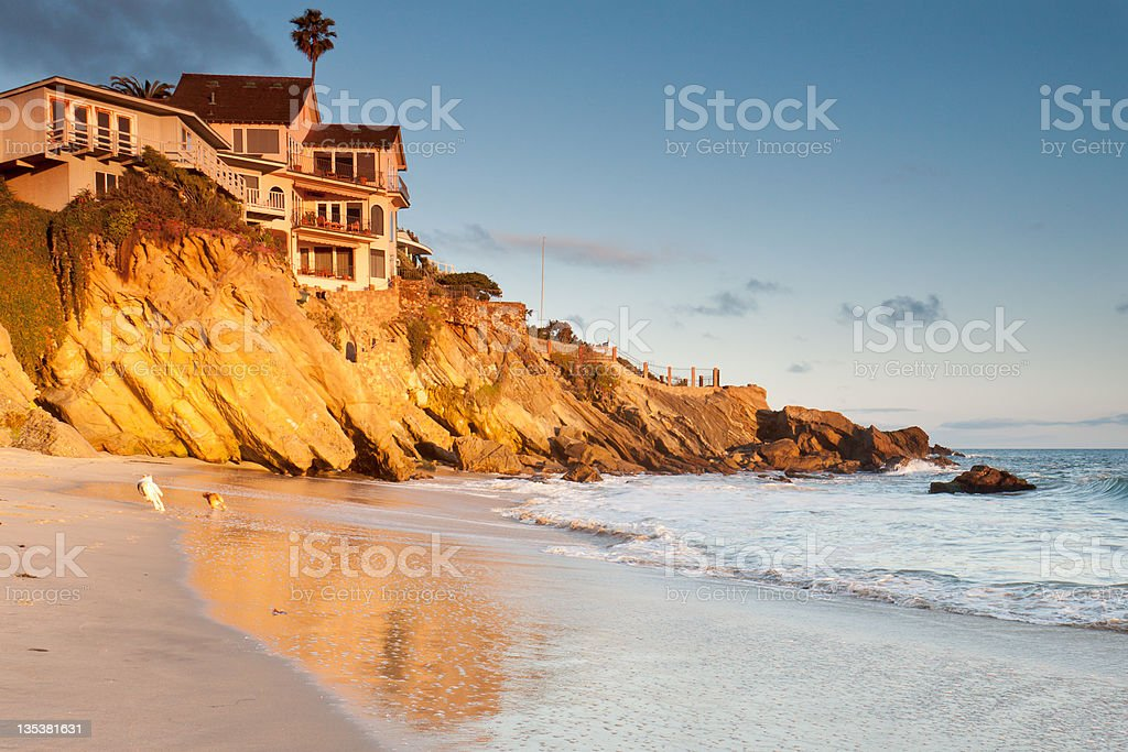 House on cliffs with playing dogs stock photo