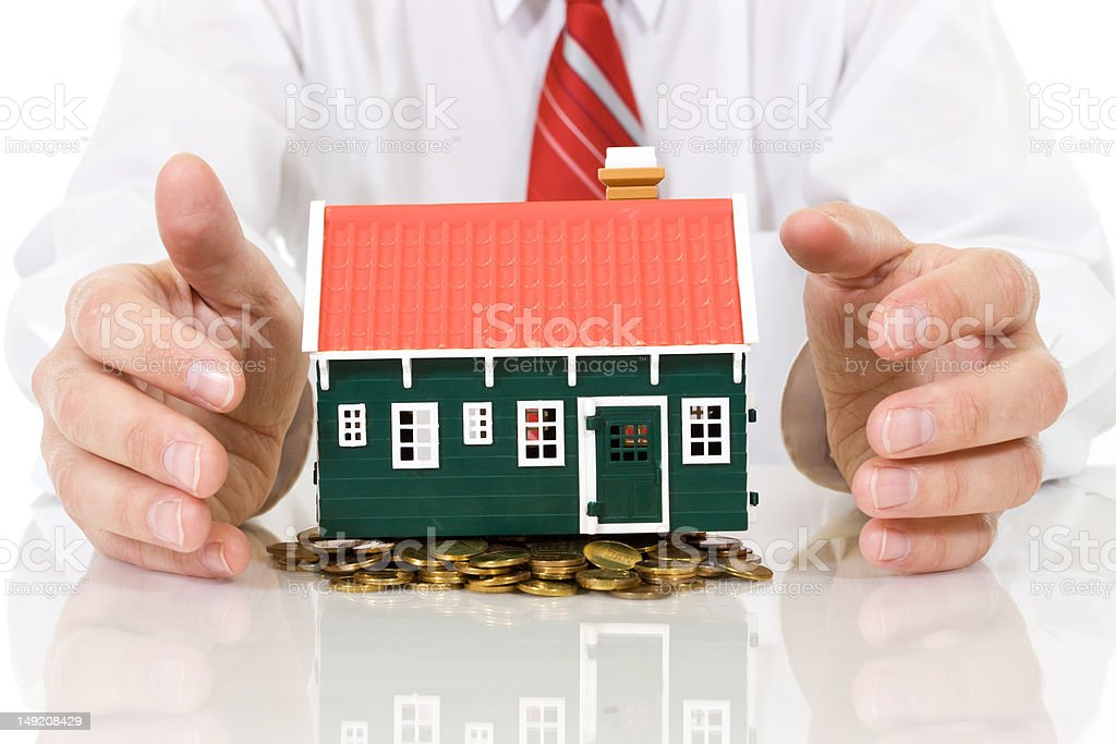 House on golden coins pile with businessman hands royalty-free stock photo
