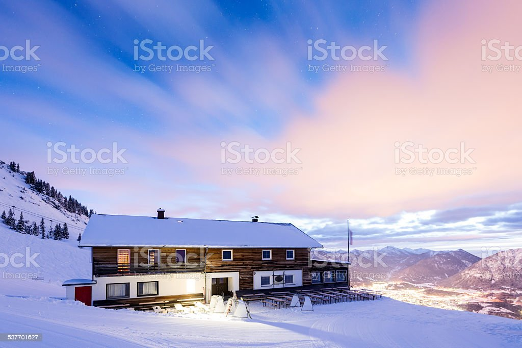 house on mountain with view to valley at snowy winter stock photo