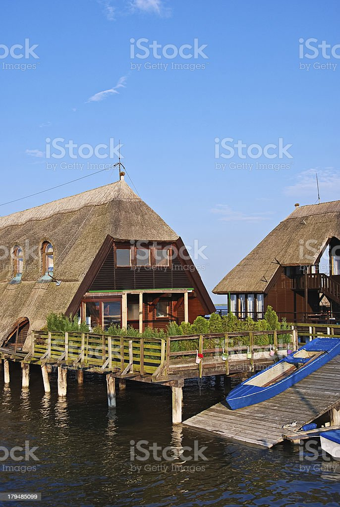House on the lake roof of reed stock photo