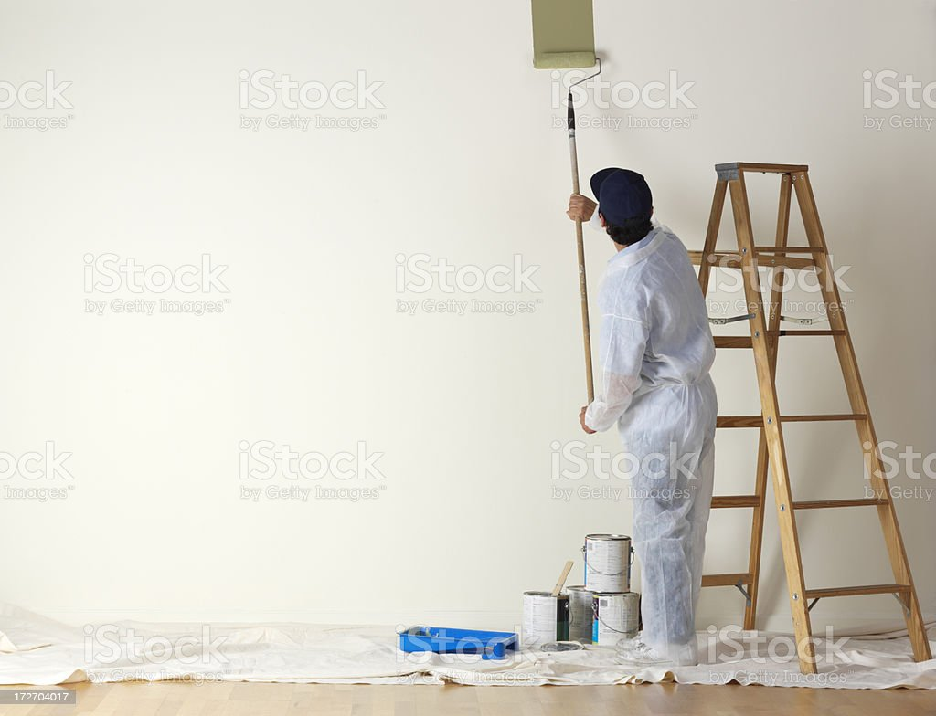 House painter beginning to paint a large wall stock photo