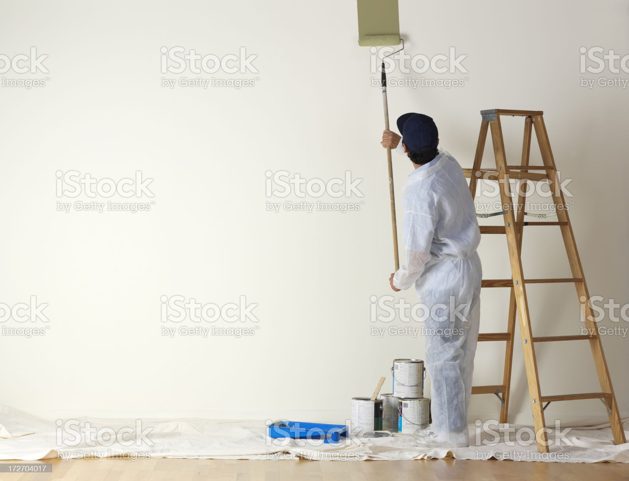 House painter beginning to paint a large wall royalty-free stock photo