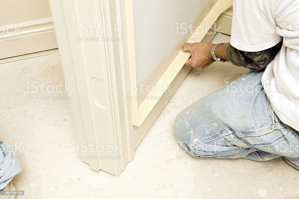 House Painter Masking Base Trim Near Floor stock photo