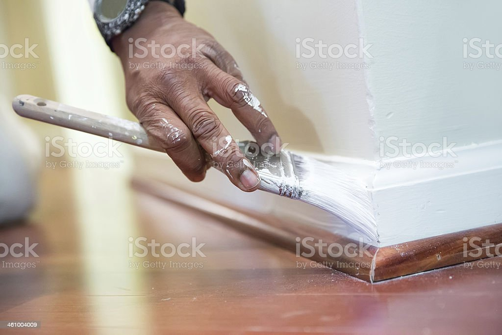 House painter paints baseboard in a home stock photo