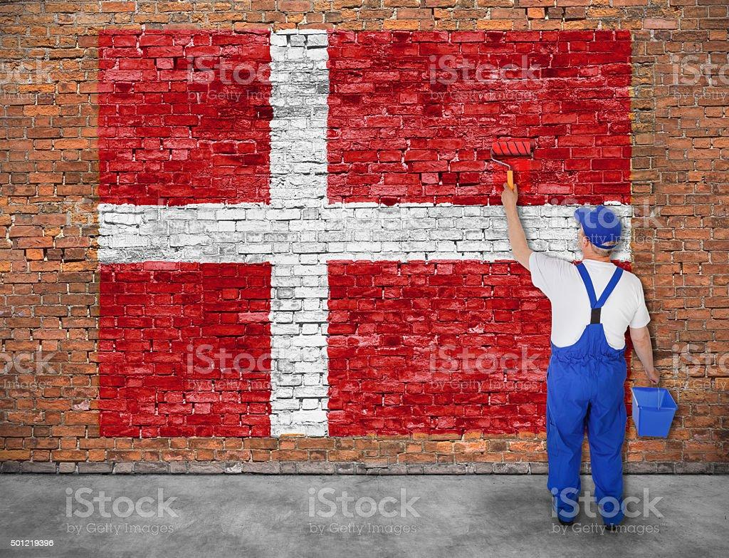 House painter paints flag of Denmark stock photo