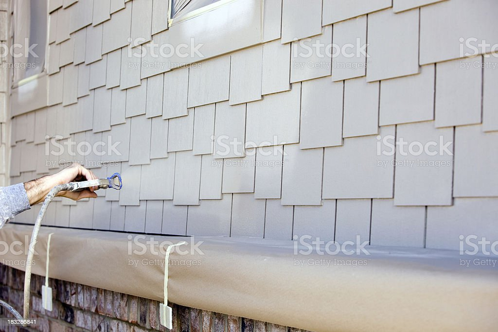 House Painter Spraying Paint on New Siding royalty-free stock photo