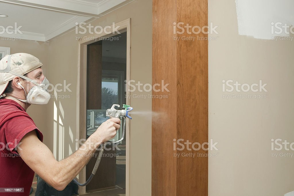 House Painter Spraying Polyurethane on Stained Cherry Column royalty-free stock photo