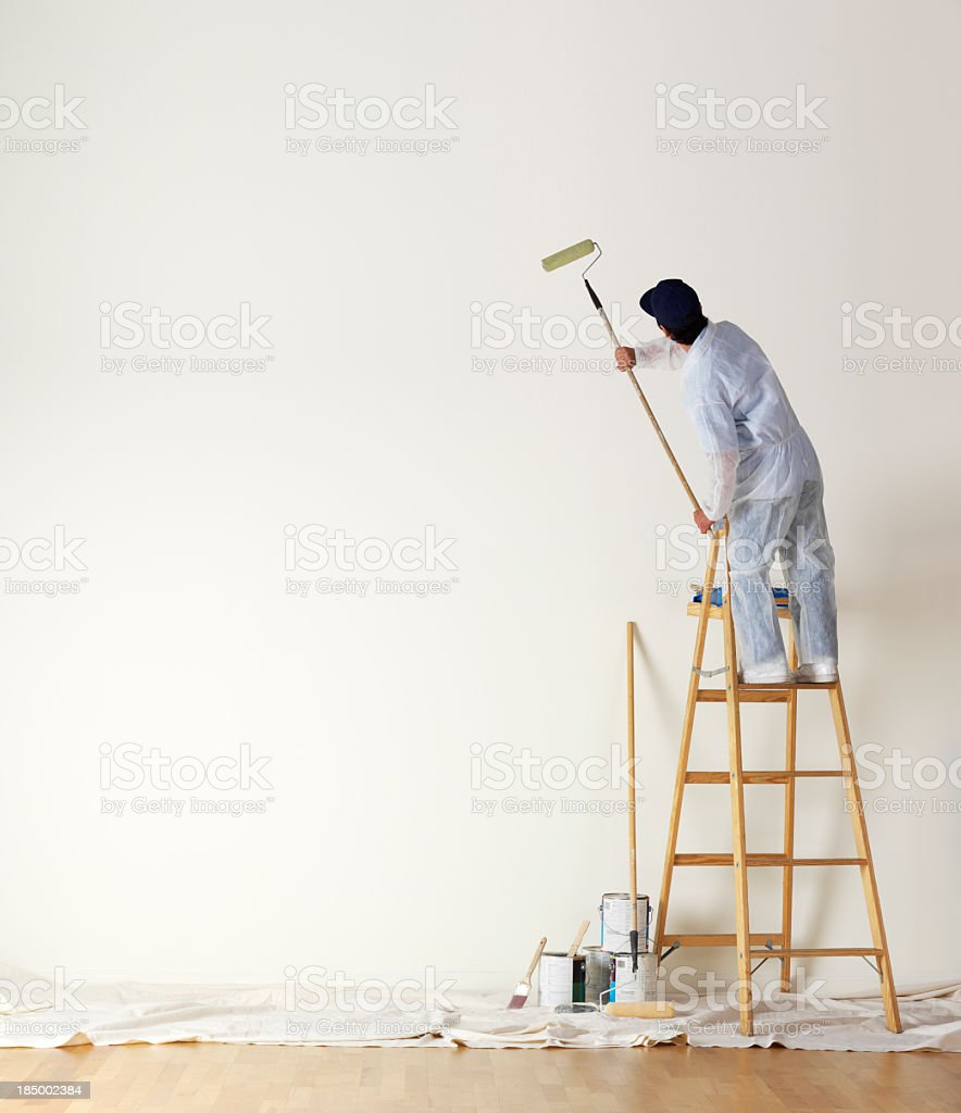 House painter standing on ladder painting a large wall stock photo