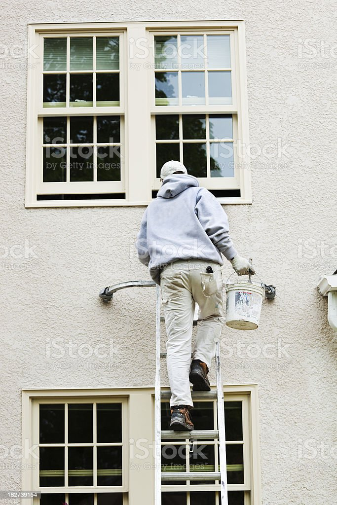 House Painter Up on Ladder Painting Exterior Window Frame Vt royalty-free stock photo