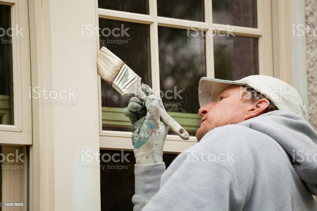 House Painter Working on Exterior Home Maintenance Improvement Painting Work stock photo