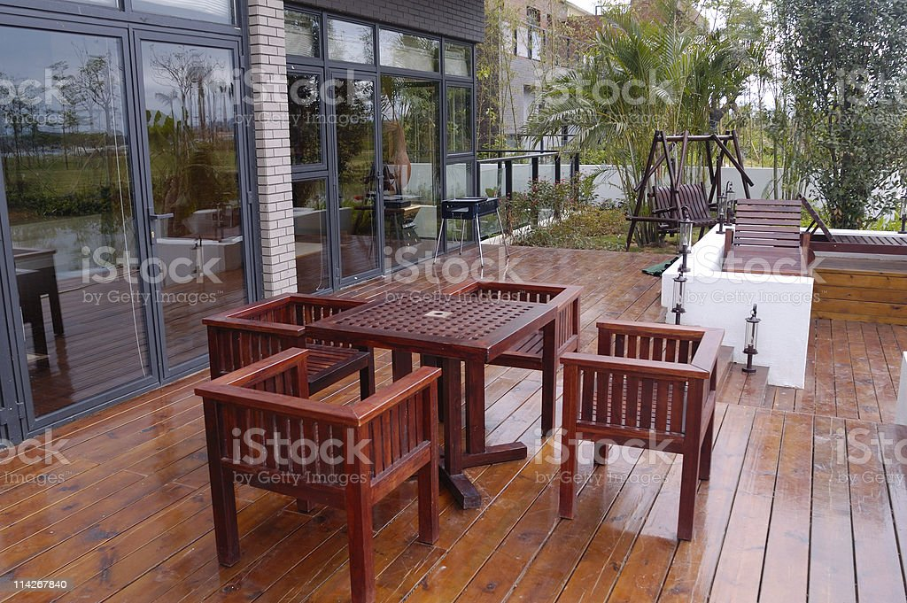 House patio with wooden table and chairs stock photo