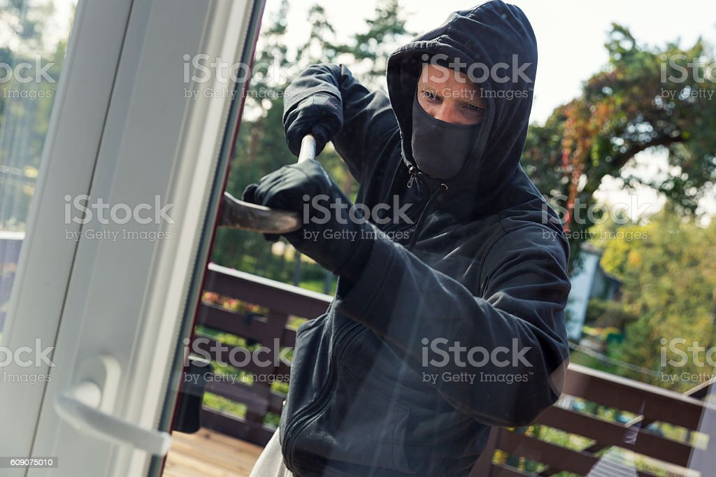 house robbery - burglar opens balcony doors with crowbar stock photo