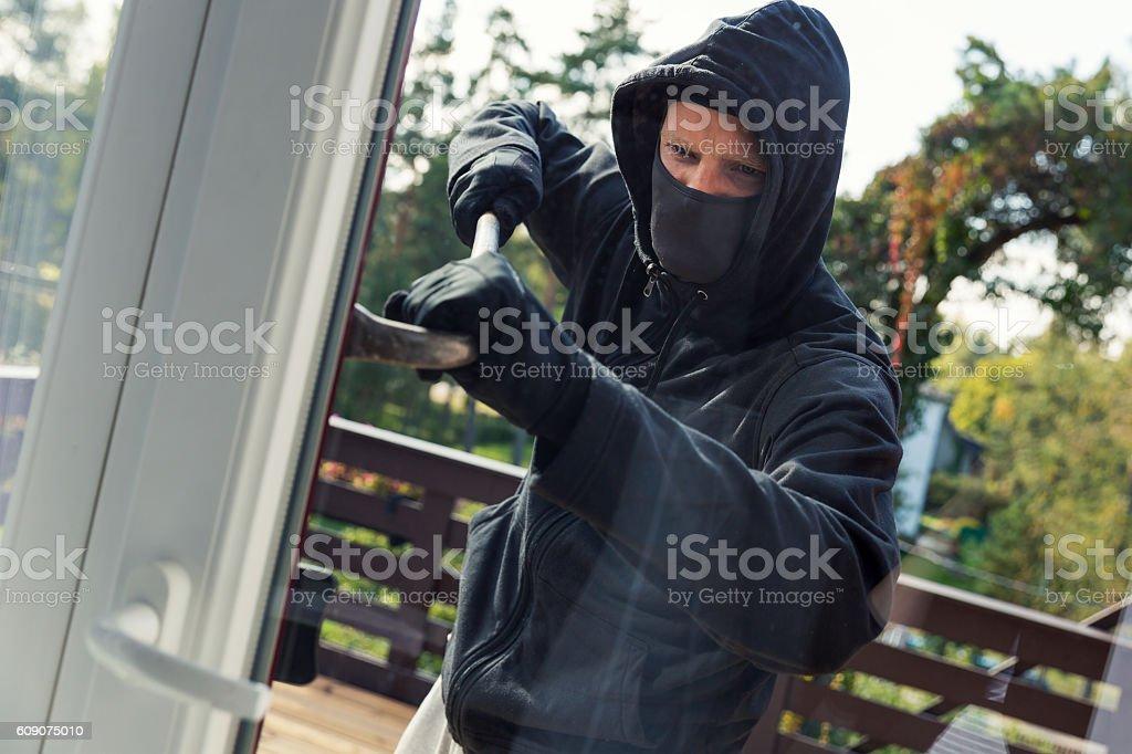 house robbery - burglar opens balcony doors with crowbar stock photo