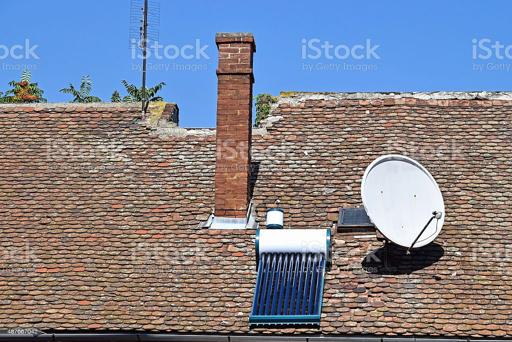 House roof with satellite dish and solar heater stock photo