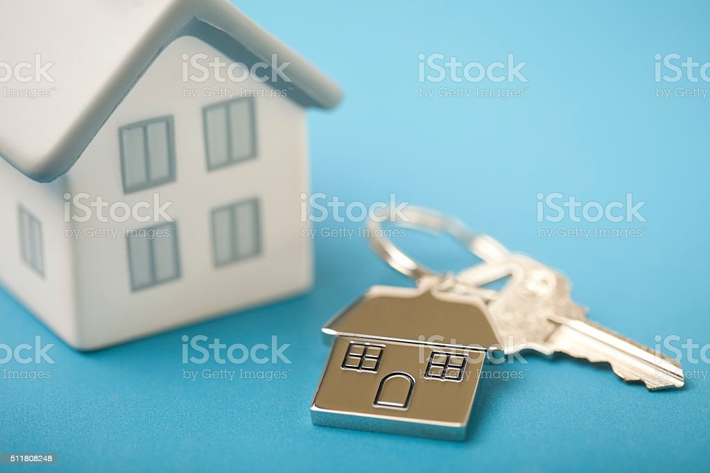 House shaped key chain on blue with house stock photo
