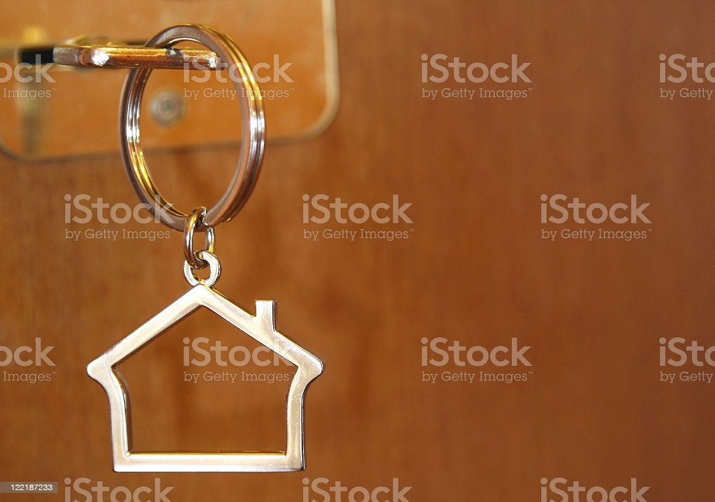 House shaped keychain hanging on a wooden key hood royalty-free stock photo