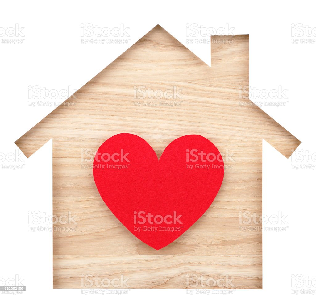 House shaped paper cutout and heart on natural wood lumber. stock photo
