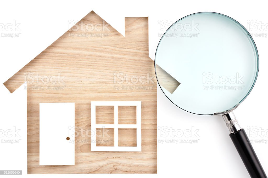 House shaped paper cutout and magnifier on natural wood lumber. stock photo