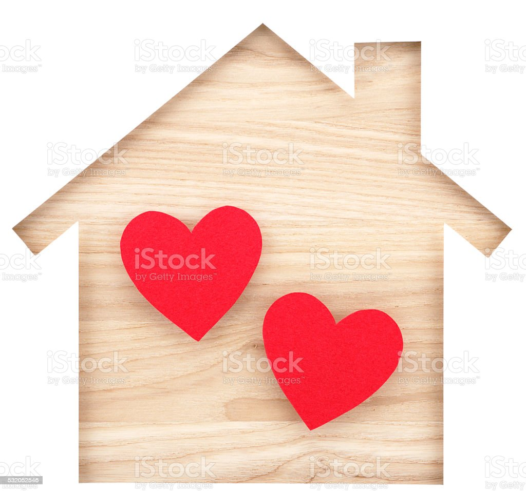 House shaped paper cutout and two hearts on wood lumber. stock photo