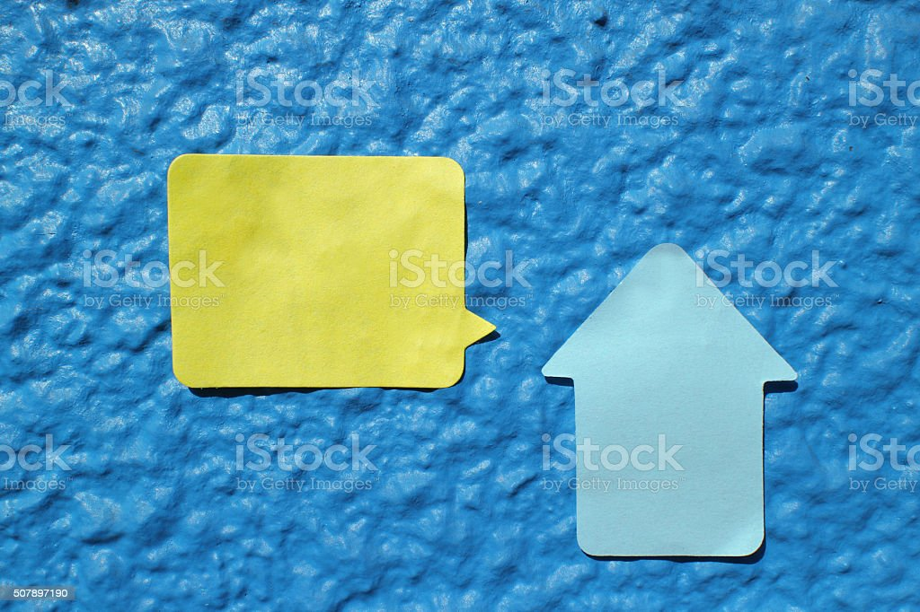 house shaped sticker note on the blue wall stock photo
