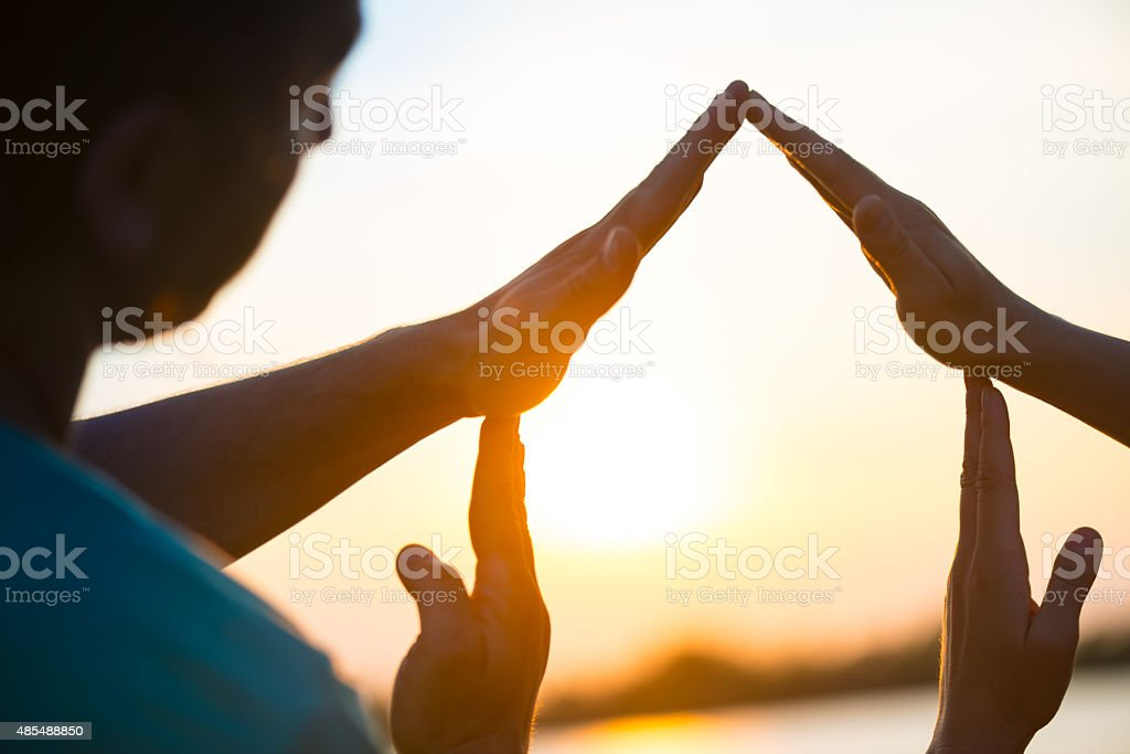 house symbol with hands against  sunset stock photo