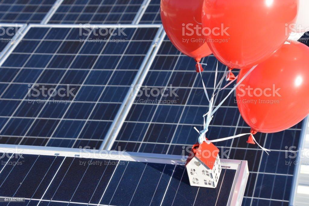 House tied  to helium balloon On solar roof stock photo